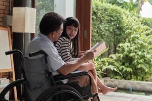 Enkelin saß im Rollstuhl auf dem Schoß des alten asiatischen Großvaters. foto
