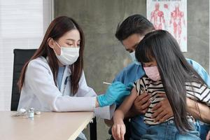 Ärztin impfen asiatisches Mädchen in der Kinderklinik. foto
