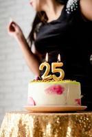 Frau im schwarzen Partykleid zündet Kerzen auf Geburtstagstorte an foto