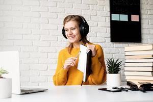 Frau mit Kopfhörern, die online mit Laptop im Notizbuch schreibt foto