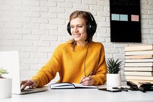 Frau, die online mit Laptop studiert, schreibt im Notizbuch foto