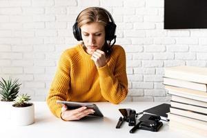 Frau in schwarzen Kopfhörern, die online mit digitalem Tablet studiert foto