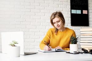 Frau im Pullover, die online mit Laptop im Notizbuch schreibt foto