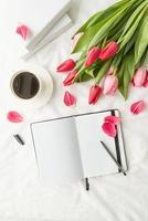 Geöffnetes leeres Notizbuch mit Tulpen und Tasse Kaffee auf weißem Bett foto