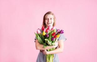 Frau mit Strauß frischer Tulpen auf rosa Hintergrund isoliert foto