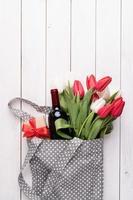 graue Stofftasche voller bunter Tulpen und Weinflasche foto