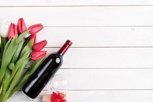 Bündel bunte Tulpen und Weinflasche auf weißem hölzernem Hintergrund foto