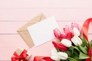 Grußkarte und Umschlag mit bunten Frühlingstulpen Draufsicht foto