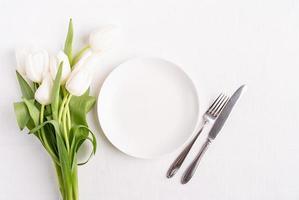 festliche Tischdekoration in Weiß, weißer Teller und Tulpen foto