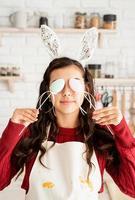 Frau mit Hasenohren, die die Augen mit Ostereidekorationen bedeckt foto