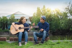 Freunde spielen zusammen im Freien Gitarre, ruhen sich in den Sommerferien aus foto