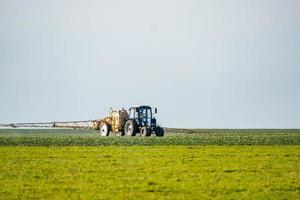 Traktor bewässert das Feld foto