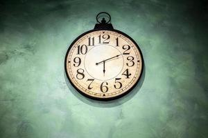Vintage-Uhr hängt an grüner Wand foto