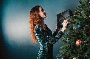 schöne Frau, die den Weihnachtsbaum mit einer Geschenkbox schmückt foto