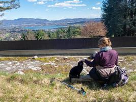 Mädchen sitzt auf dem Boden und streichelt eine schwarze Katze in den Bergen foto