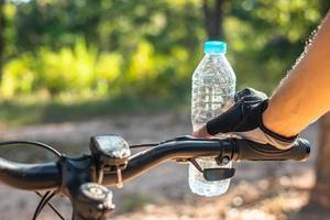 Radfahrer stehen oben auf dem Berg und tragen eine Flasche Wasser. foto