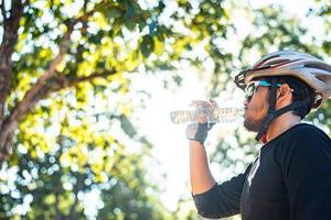 Radfahrer stehen oben auf dem Berg und trinken eine Flasche Wasser. foto