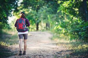 Rückseite der jungen Frau Wanderer mit Rucksack zu Fuß auf einem Feldweg. foto