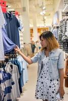 glückliche junge Frau, die Kleidungsverkauf im Geschäft betrachtet. foto