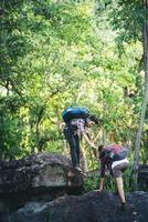Wandererfrau, die Hilfe bei der Wanderung lächelt, glücklich, Hindernis zu überwinden. foto