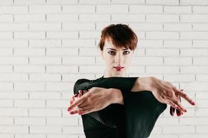 hübsche Frau im schwarzen Kleid, tanzend mit roten Kastagnetten, hoher Schlüssel foto