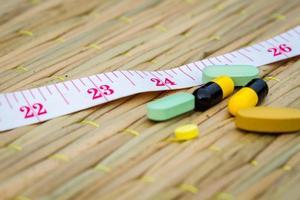 Pillen und Maßband auf traditioneller Matte. foto