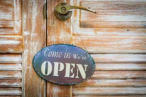 komm rein wir haben die Holztür geöffnet foto