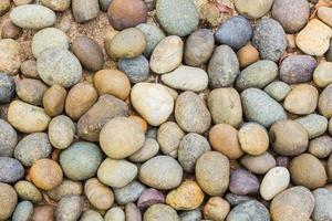 Kieselsteine in vielen Formen am Strand, abstrakter Hintergrund foto