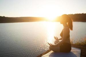 Junge gesunde Frau praktiziert Yoga am Bergsee während des Sonnenuntergangs. foto