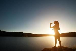 Silhouette der Sportfrau wandert zum Gipfel des Bergsonnenuntergangs foto