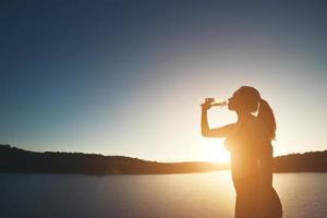 Frau wandert auf den Gipfel des Berges und trinkt Wasser bei Sonnenuntergang foto