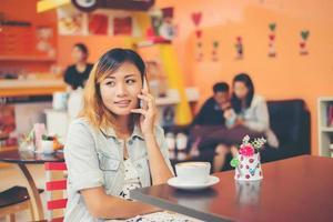 Junge schöne Frau, die im Café telefoniert, sieht so glücklich aus. foto