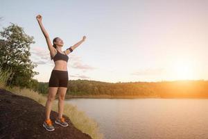Junge Fitness-Frau erreicht Wandern auf dem Gipfel mit Seeblick Sonnenuntergang. foto