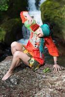 Jala Neti Nasenspülung mit einem Mädchen in der Nähe eines Wasserfalls foto