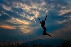 Sprung in die Berge in der Abenddämmerung Mädchen in Silhouette foto