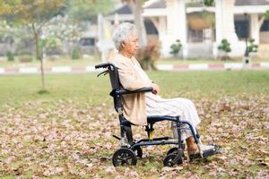 asiatische senior oder ältere alte damenpatientin schmerzt ihr knie im rollstuhl im park, gesundes starkes medizinisches konzept. foto