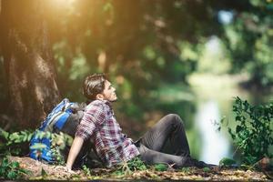Junge müde mit Rucksack, der auf dem Gras sitzt und während der Wanderungen ausruht foto