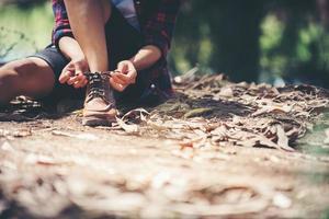 Frau Wanderer hält an, um ihren Schuh auf einem Sommerwanderweg im Wald zu binden. foto