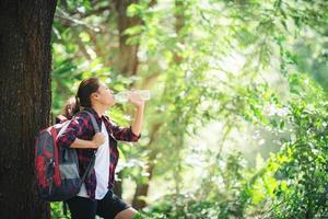 Frau, die eine Pause macht und eine Flasche Wasser trinkt, wandert im Wald. foto