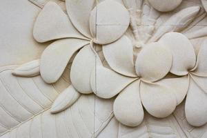 Nahaufnahme Plumeria geschnitzten Steinmauern, Hintergrund foto