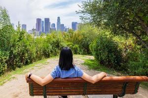 Frau sitzt auf dem Stuhl und sieht die Skyline foto