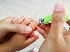 Nahaufnahme Mutter schneidet Fingernägel für ihr Baby foto