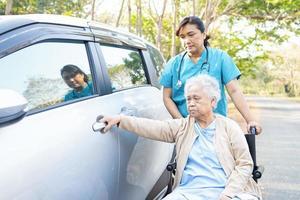 helfen und unterstützen Sie asiatische ältere Patientin im Rollstuhl, um zum Auto zu gelangen foto
