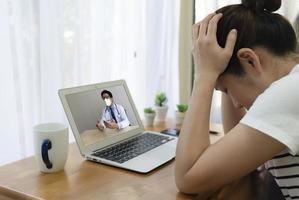 Patient, der Kopfschmerzen hat, Arzt per Videoanruf aufsuchen foto