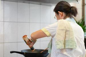Senior asiatische Frau, die Pasta zum Mittagessen in der Küche kocht foto