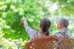 Seniorenpaar sitzt auf einer Bank im Garten und genießt die Natur zusammen foto