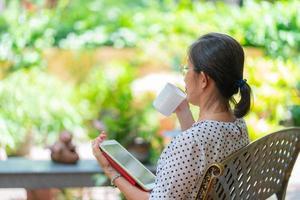 Ältere asiatische Frau, die Kaffee trinkt, während sie Tablet verwendet, um E-Mails zu lesen? foto