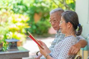 älteres asiatisches paar mit tablet zusammen zu hause foto
