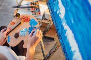 Künstlerin, die Ölfarben auf Palette mischt, die in ihrer Hand hält foto