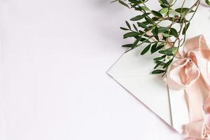 Umschlag auf weiß-rosafarbenem Hintergrund mit pfirsichfarbenem Seidenband und rosa foto